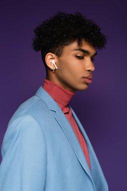 happy african american man in wireless earphones on purple