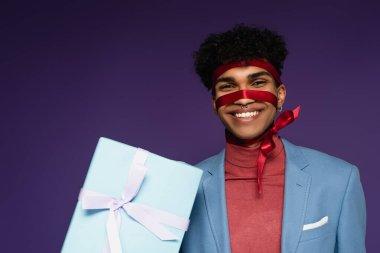 Joyful african american man tied with ribbon near present on purple stock vector