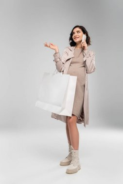 Happy pregnant woman talking on cellphone and holding shopping bag on grey background stock vector