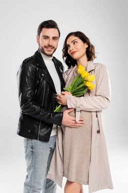 Smiling man in leather jacket hugging pregnant wife with tulips on grey background stock vector