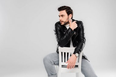 Stylish man sitting on white chair isolated on grey stock vector