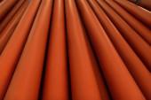 Hintergrund aus hellen, roten Kunststoffrohren mit Kopierraum