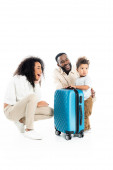 laughing african american man hugging son near happy wife and suitcase on white