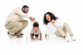 african american man holding paper roof above crawling son near laughing wife on white