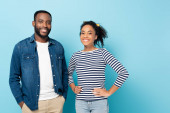 veselý africký americký pár usmívá na kameru, zatímco stojí na modré