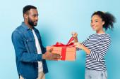 vidám afro-amerikai nő nyitó ajándék közelében mosolygó férj a kék
