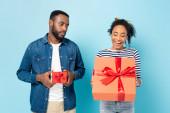 megsértett afro-amerikai férfi kis ajándék doboz nézi a csodálkozó feleség nagy ajándék a kék