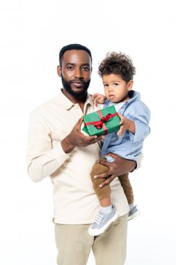Young african american man holding toddler son and gift box isolated on white stock vector