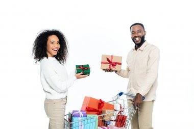 Cheerful african american couple looking at camera while holding gift boxes near shopping cart isolated on white stock vector