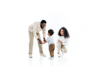 Happy african american father holding hands of little son near laughing wife on white stock vector
