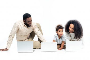 Amazed african american kid looking away near happy parents and laptops on white stock vector