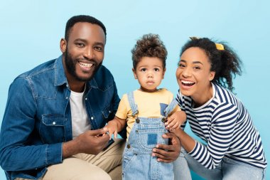 Joyful african american couple with toddler son smiling at camera isolated on blue stock vector