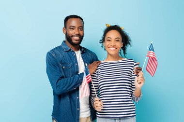 Happy african american couple holding small flags of usa while smiling at camera isolated on blue stock vector