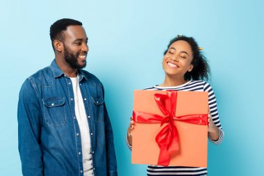 Happy african american woman holding big gift box near smiling husband on blue stock vector