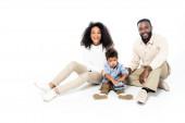 africký americký chlapec drží dárkové krabice v blízkosti veselých rodičů na bílém
