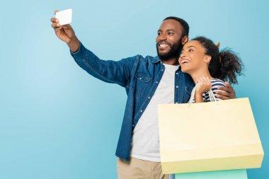 Mutlu Afro-Amerikalı adam, neşeli karısıyla selfie çekiyor. Elinde mavi torbalarla.