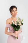 hezká žena v růžových šatech a závoj drží svatební kytice při úsměvu na kameru izolované na šedé