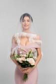 hezká žena v růžových šatech a závoj drží svatební kytice izolované na šedé