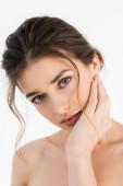 sinnliche Frau mit natürlichem Make-up, die Gesicht berührt, während sie die Kamera isoliert auf Weiß betrachtet