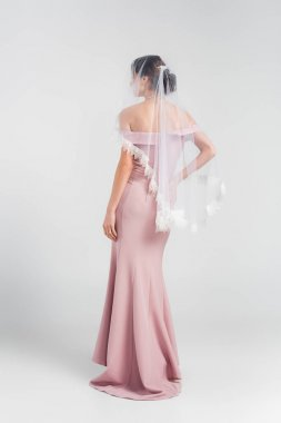 Full length view of bride in pink dress and veil posing on grey stock vector