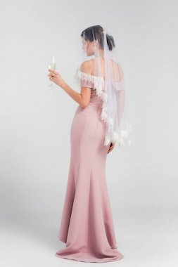 Full length view of woman in wedding dress and veil holding glass of champagne on grey stock vector