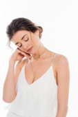 charming fiancee holding hand near face while posing with closed eyes isolated on white