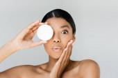überrascht afrikanisch-amerikanische Frau, die Augen bedeckt, während sie Behälter mit Gesichtscreme isoliert auf grau hält