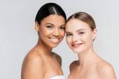 pozitivní mezirasové ženy se usmívají při pohledu na kameru izolované na šedé