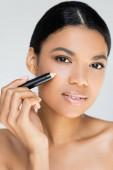 Afrikanisch-amerikanische junge Frau hält Concealer isoliert auf grau