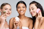 boldog többnemzetiségű nők mosolygott, miközben a gazdaság tartály kozmetikai krém, jáde görgő és szilikon tisztító elszigetelt szürke