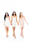 full length of cheerful multiethnic women in dresses holding hands and walking isolated on white