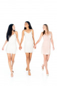 full length of happy interracial women in dresses holding hands isolated on white