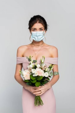 Young fiancee in medical mask holding wedding bouquet isolated on grey stock vector