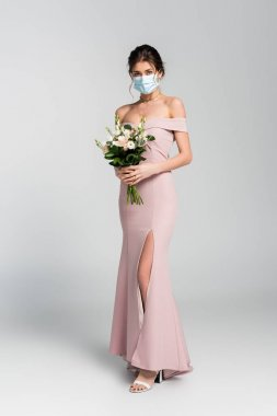 Full length view of bride in medical mask posing with wedding bouquet on grey stock vector