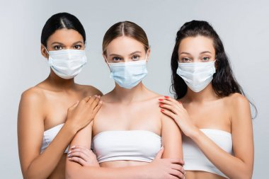 Multiethnic women in tops with bare shoulders and medical masks isolated on grey stock vector