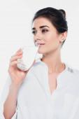 Bruneta žena drží sklenici vody a dívá se stranou izolované na bílém