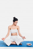 Young woman meditating near bowl of cereals with berries on fitness mat on white background