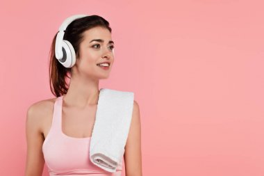 Positive sportswoman in headphones with towel isolated on pink