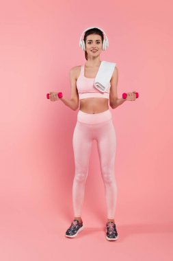 Happy sportswoman in headphones training with dumbbells on pink background