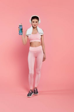 Young sportswoman in headphones and towel holding sports bottle on pink background