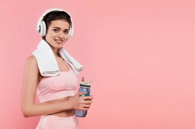 Sportswoman smiling at camera while listening music in headphones and holding sports bottle isolated on pink