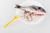 vrchní pohled na plastovou vidličku u talíře s vykuchanými rybami a cigaretovými zakončeními na bílé, koncept ekologie