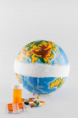 bekötözött földgömb közelében tabletták szürke háttér, ökológia koncepció