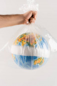 partial view of man holding plastic bag with bandaged globe isolated on grey, ecology concept