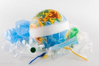 Bandaged globe near plastic garbage on grey, ecology concept stock vector