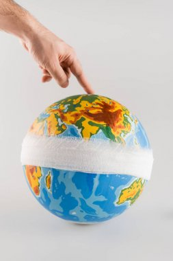 Cropped view of man touching bandaged globe on grey, ecology concept stock vector
