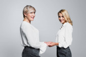 cheerful mother and daughter in white blouses holding hands isolated on grey