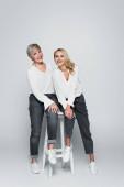 Ganzkörperansicht der modischen Mutter und Tochter, die in die Kamera schauen, während sie auf einem hohen Hocker auf grau sitzen