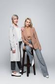 fashionable woman near stylish daughter sitting on high chair on grey