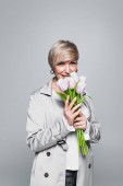 happy woman in stylish trench coat smelling fresh tulips isolated on grey
